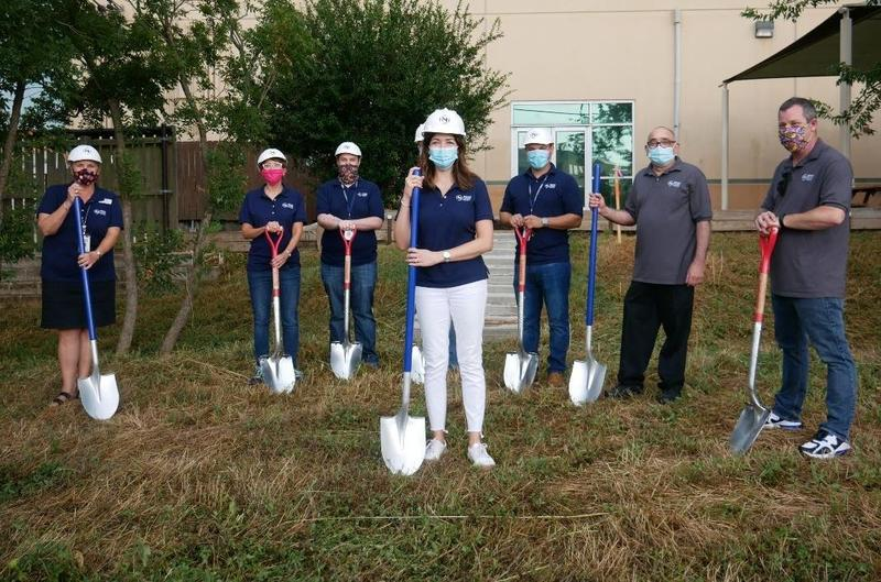 Photo of 6 NYOS senior staff and 2 NYOS board members holding shovels and wearing hard hats and masks outside of Lamar Campus at ground breaking ceremony.
