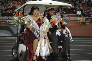 Homecoming queen and king riding on golf cart