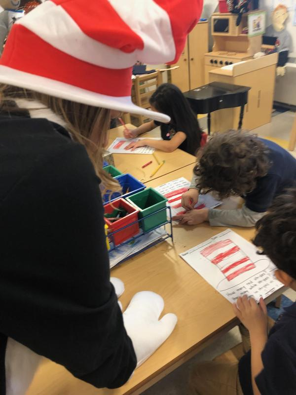 teacher looking over students coloring their hats