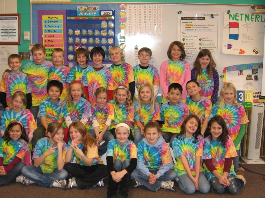 students pose for camera in tie dye shirts