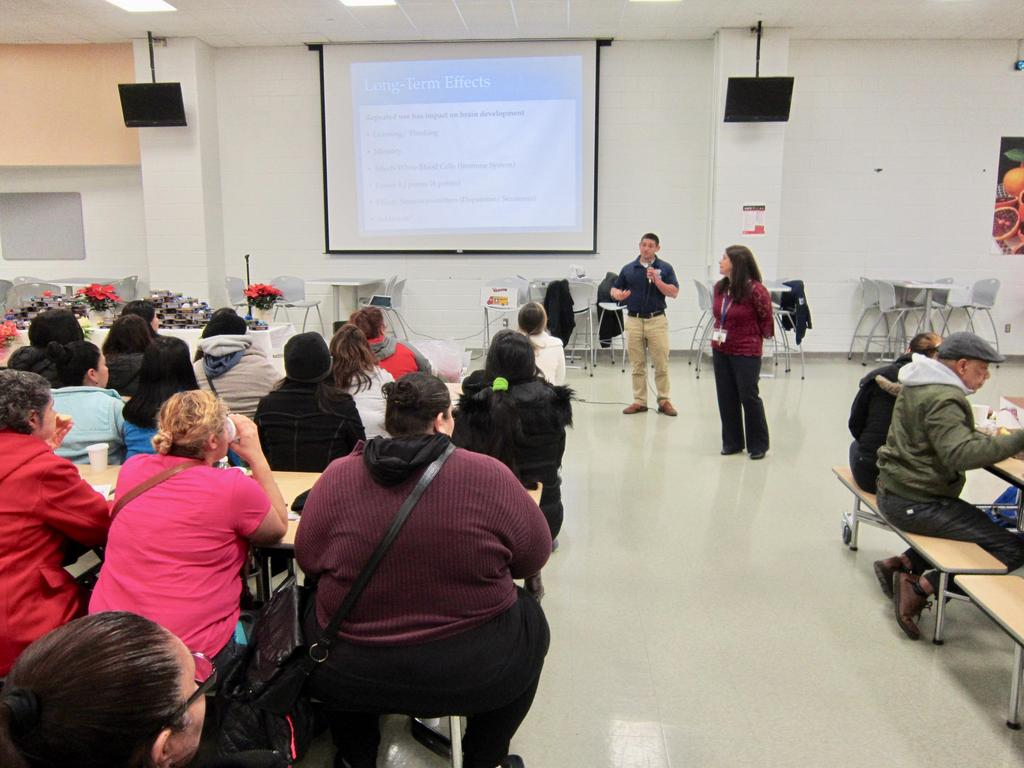 presenter roveda and parent liaison mendez talking to parents