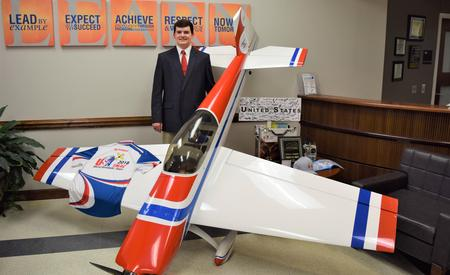 Joseph Thibodeau with aerobatic model airplane on display at the Board of Education office.