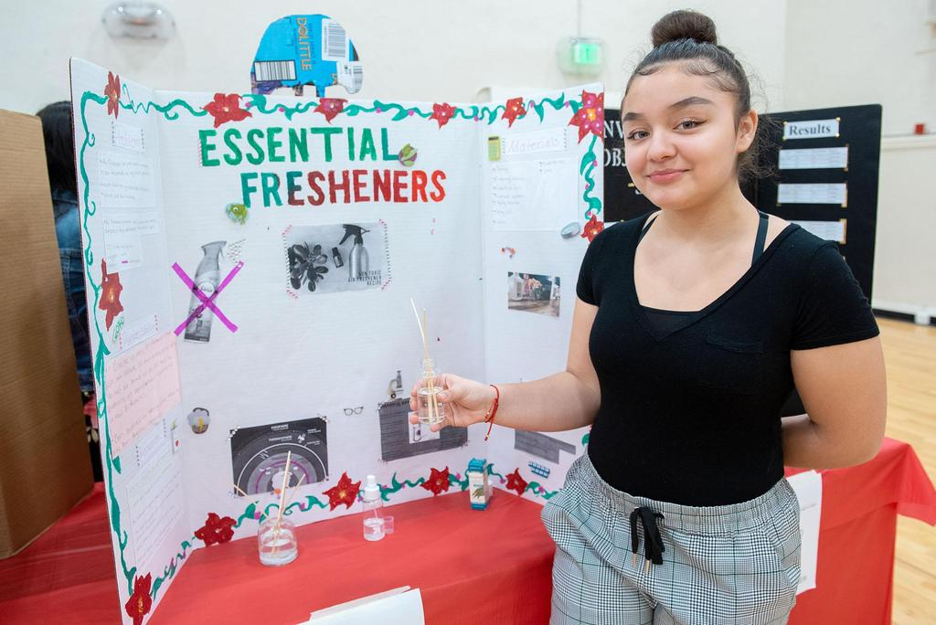 A student stands next to her project called Essential Fresheners