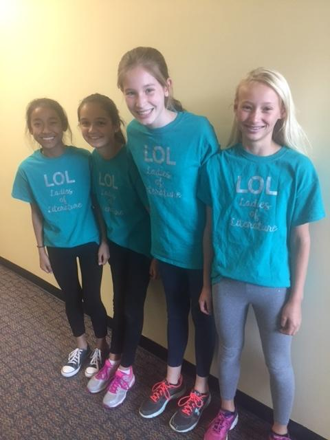 four girls in turquoise shirts smile