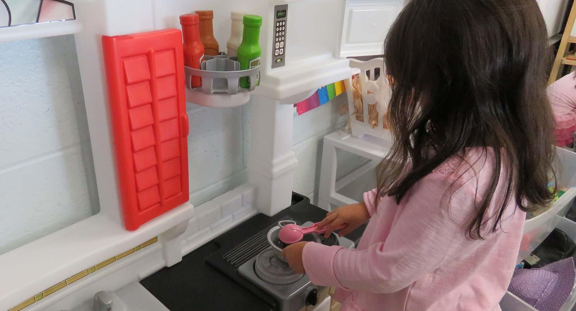 A young girl dressed in pink pretends to cook in a play kitchen.