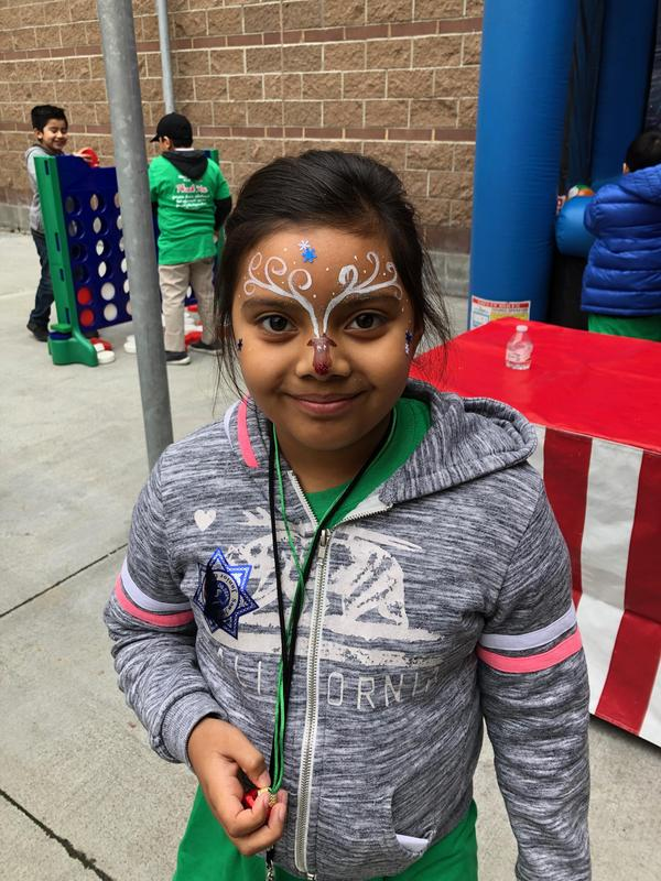 Student showing off her butterfly face paint