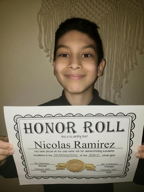 Nicolas holding honor roll certificate