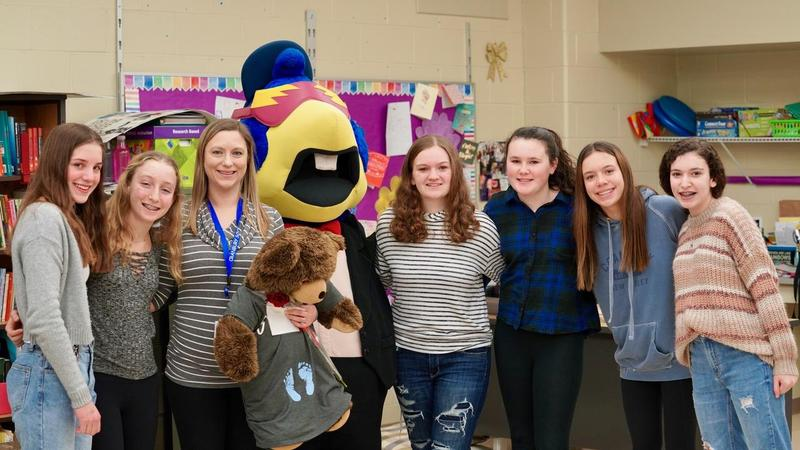 Nichole Ball stands with Trenton Thunder mascot, Boomer and members of the Kindness Club.