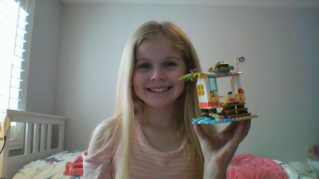 girl holding lego house