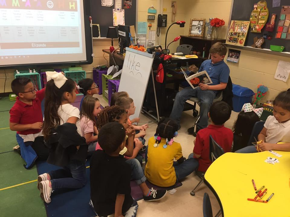 4th grade student reading to KG students