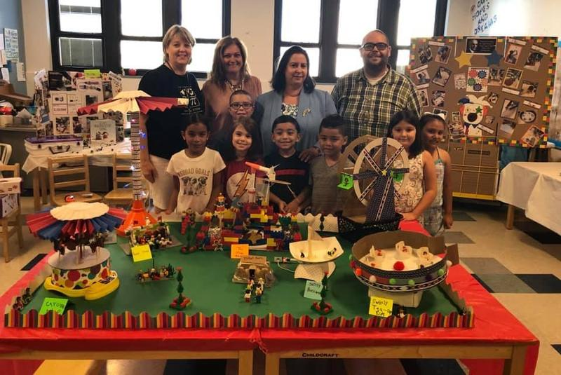 several children, Hudson Admin, Superintendent Abbato, and STEM director Navas in front of student created carousels