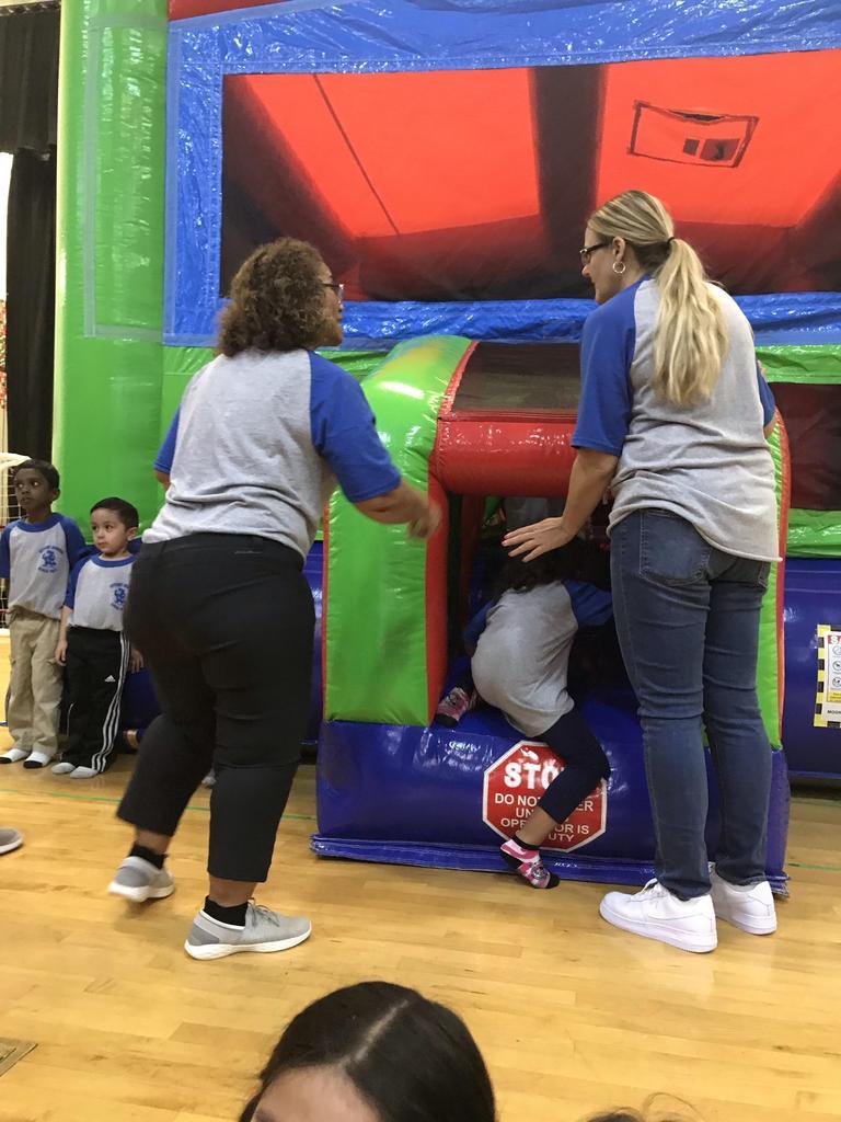 teachers helping kids enter the bouncy house