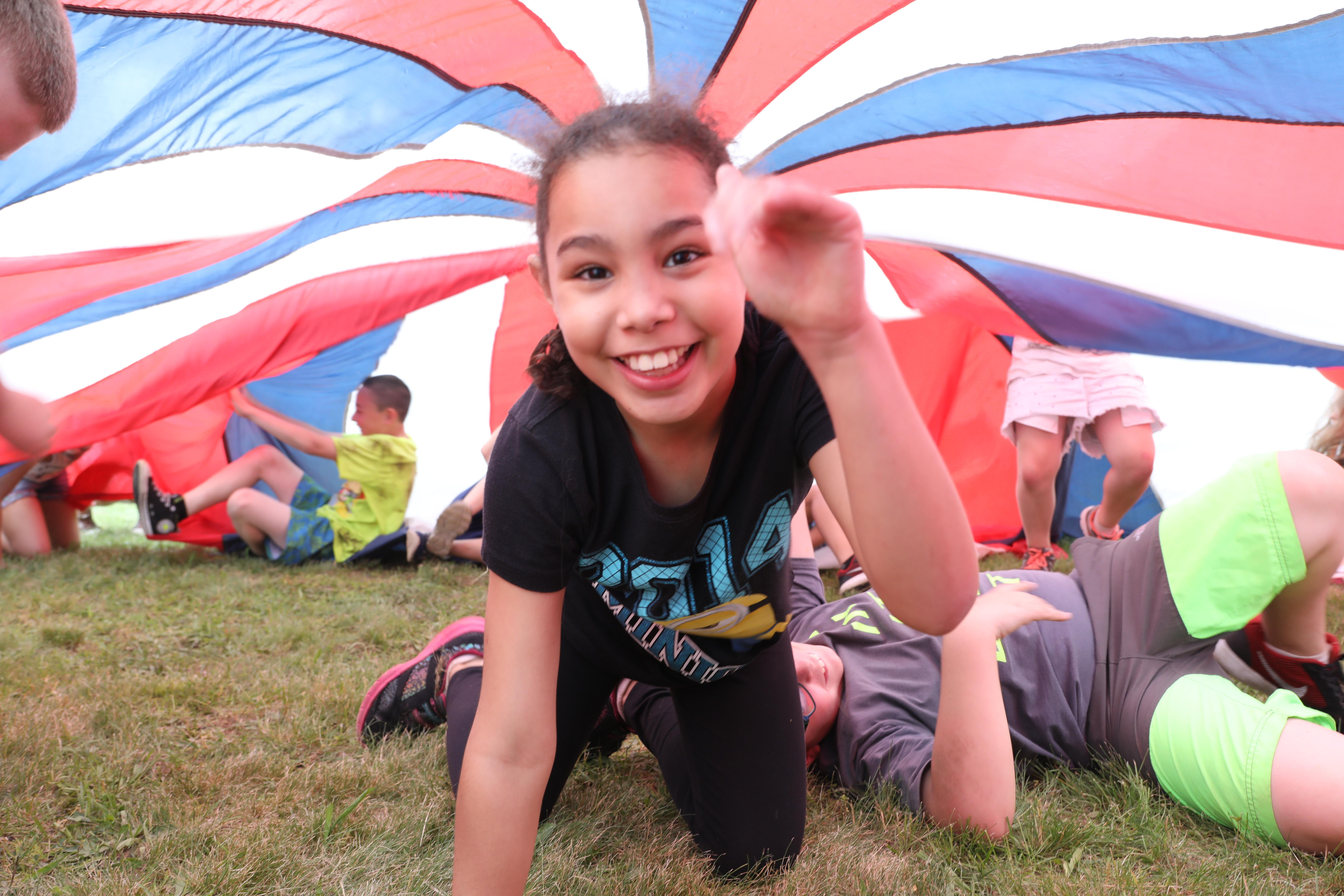 Andrew Avenue Elementary student playing under a parachute