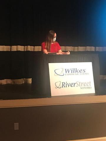 Abigal G. signing her apprenticeship paperwork with Wilkes Communications/RiverStreet Networks.