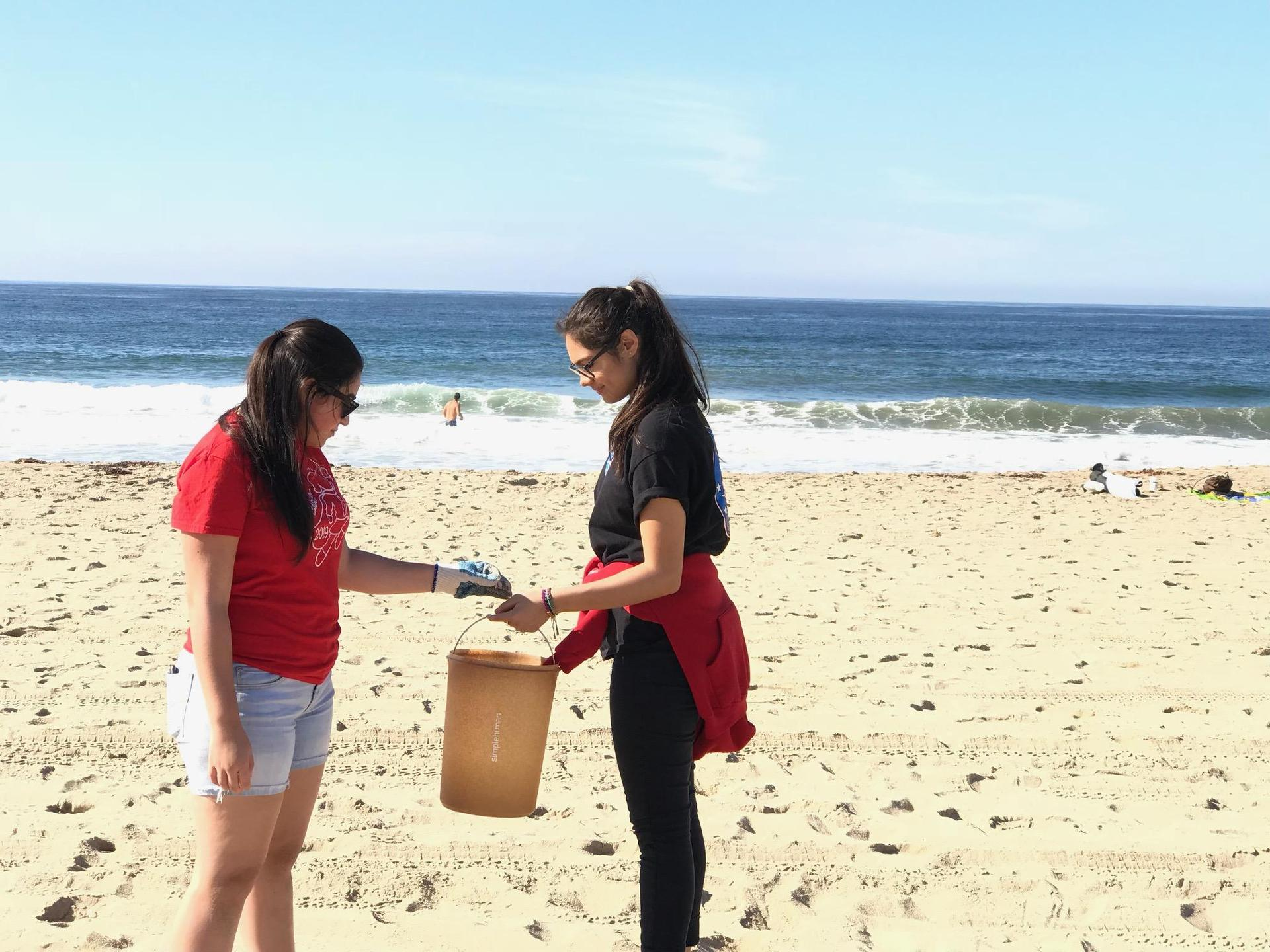 two students at a beach cleanup