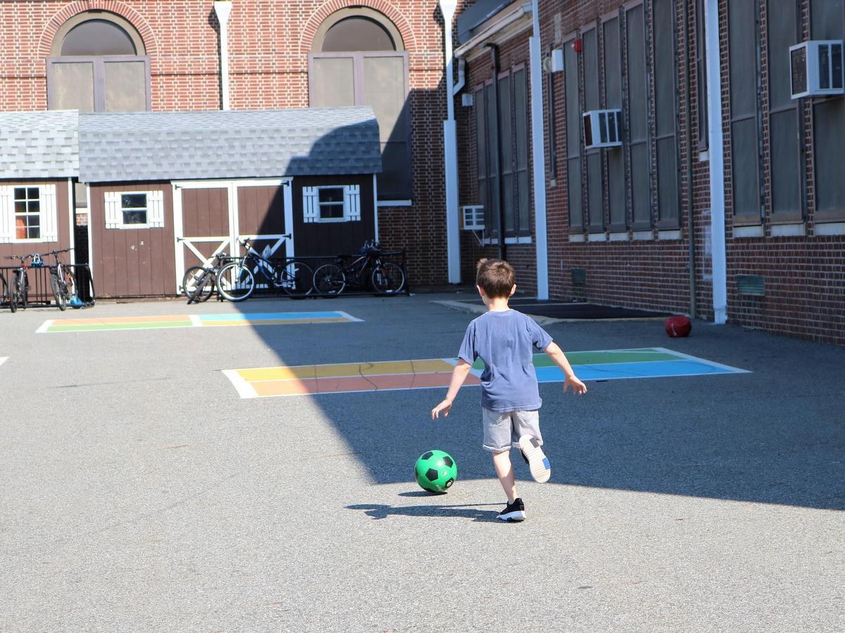 Photo of back of elementary student running and kicking a ball.