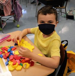 Photo of student working with manipulatives at desk.