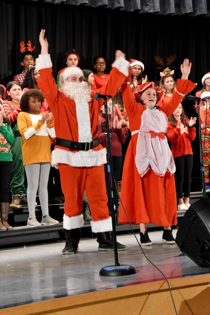 Santa Claus and Mrs. Claus raise their arms in the air