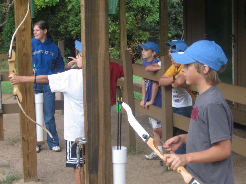 students shoot bow and arrows at camp