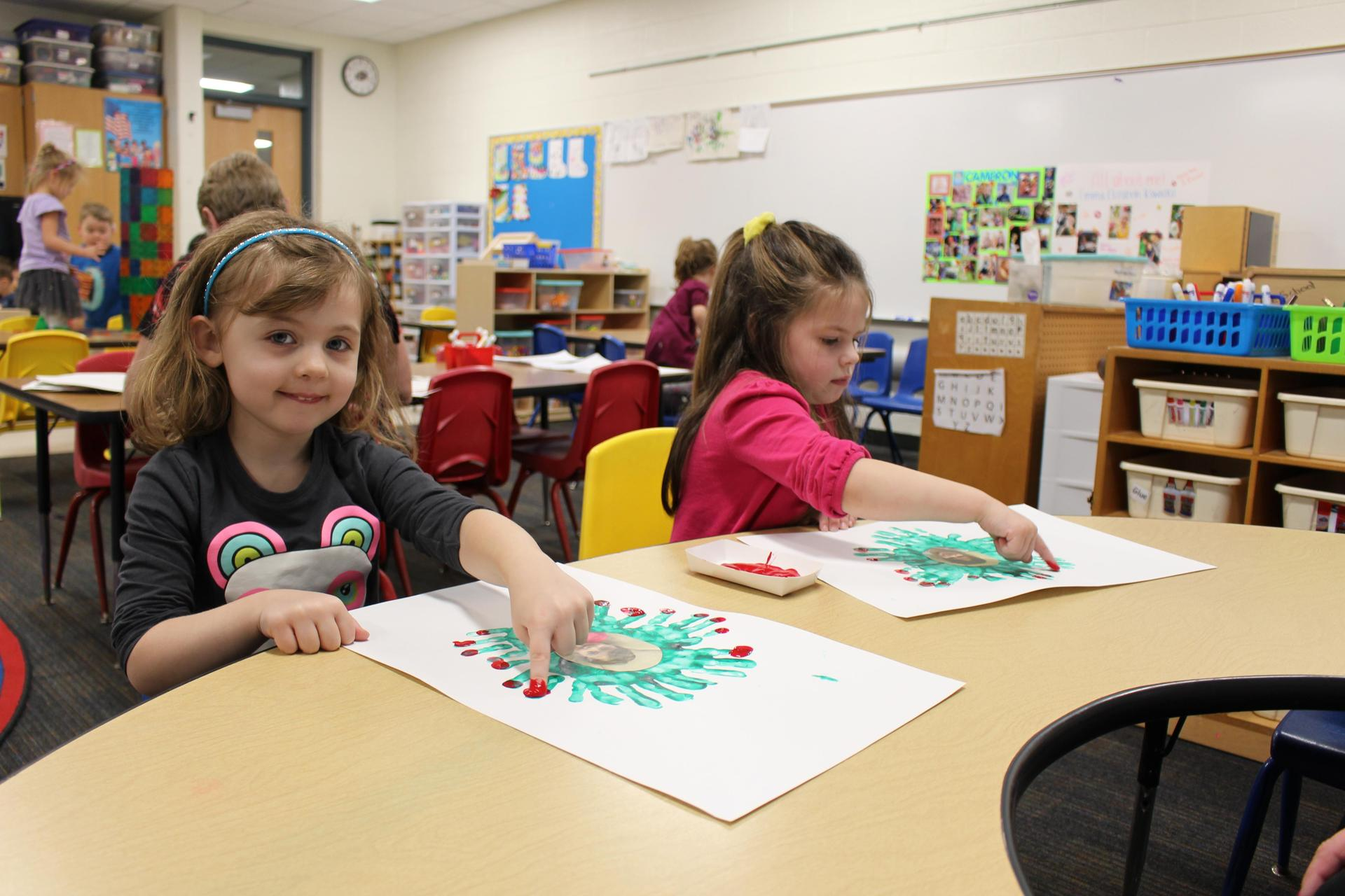 girls paint with fingerpaint at desk