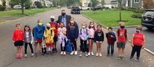 Photo of school superintendent posing with group of students on Walk to School Day