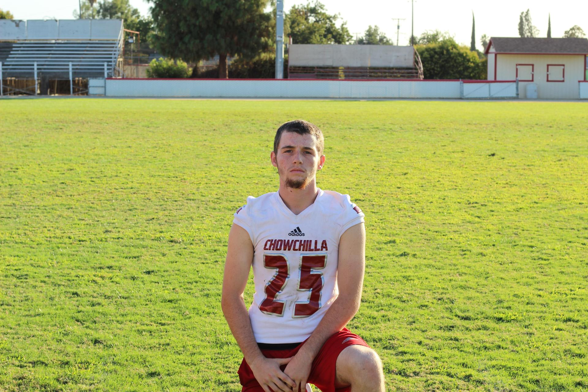 Varsity football player posing