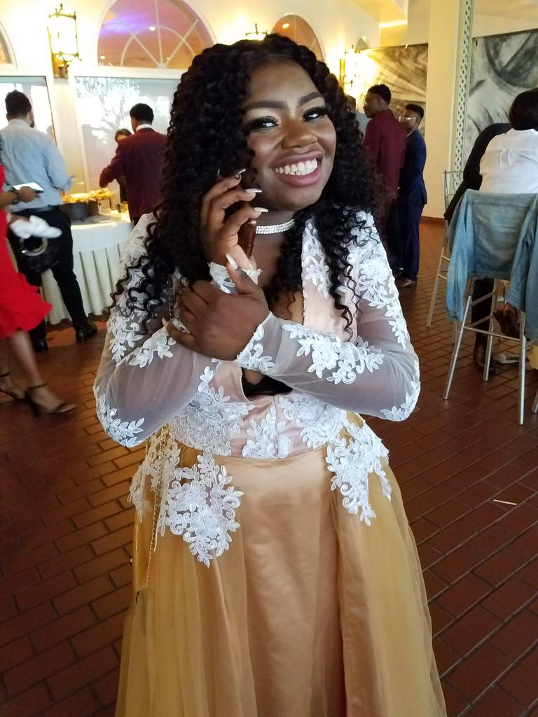 A student wearing a dress smiling