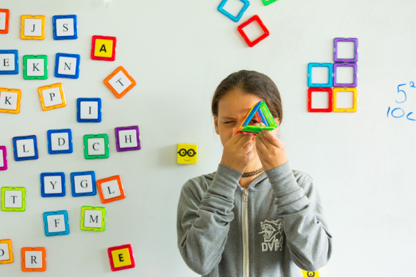 Admissions picture of girl at whiteboard looking through a 3 dimensional triangle.
