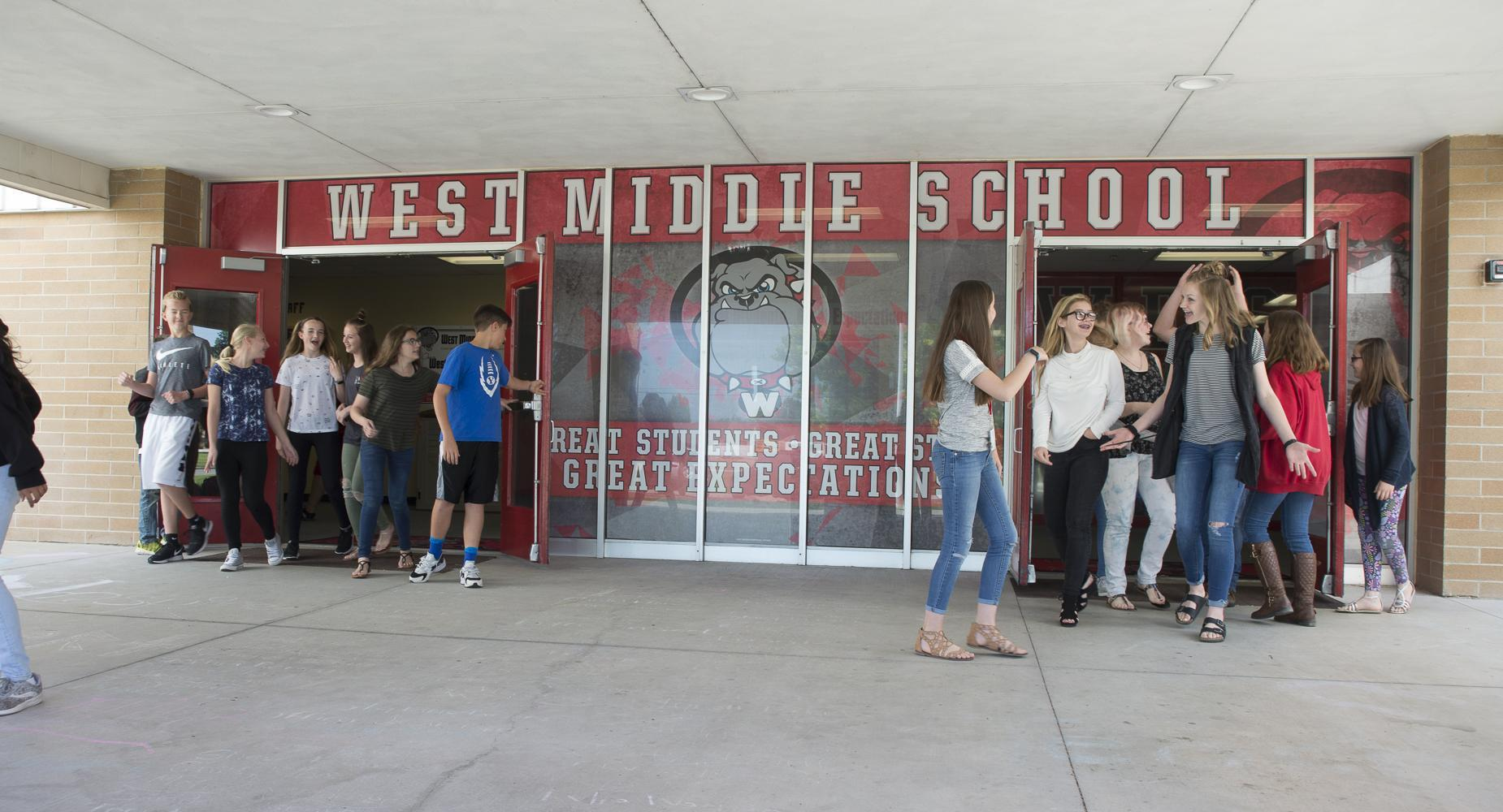 Students leave through the front entrance of the school