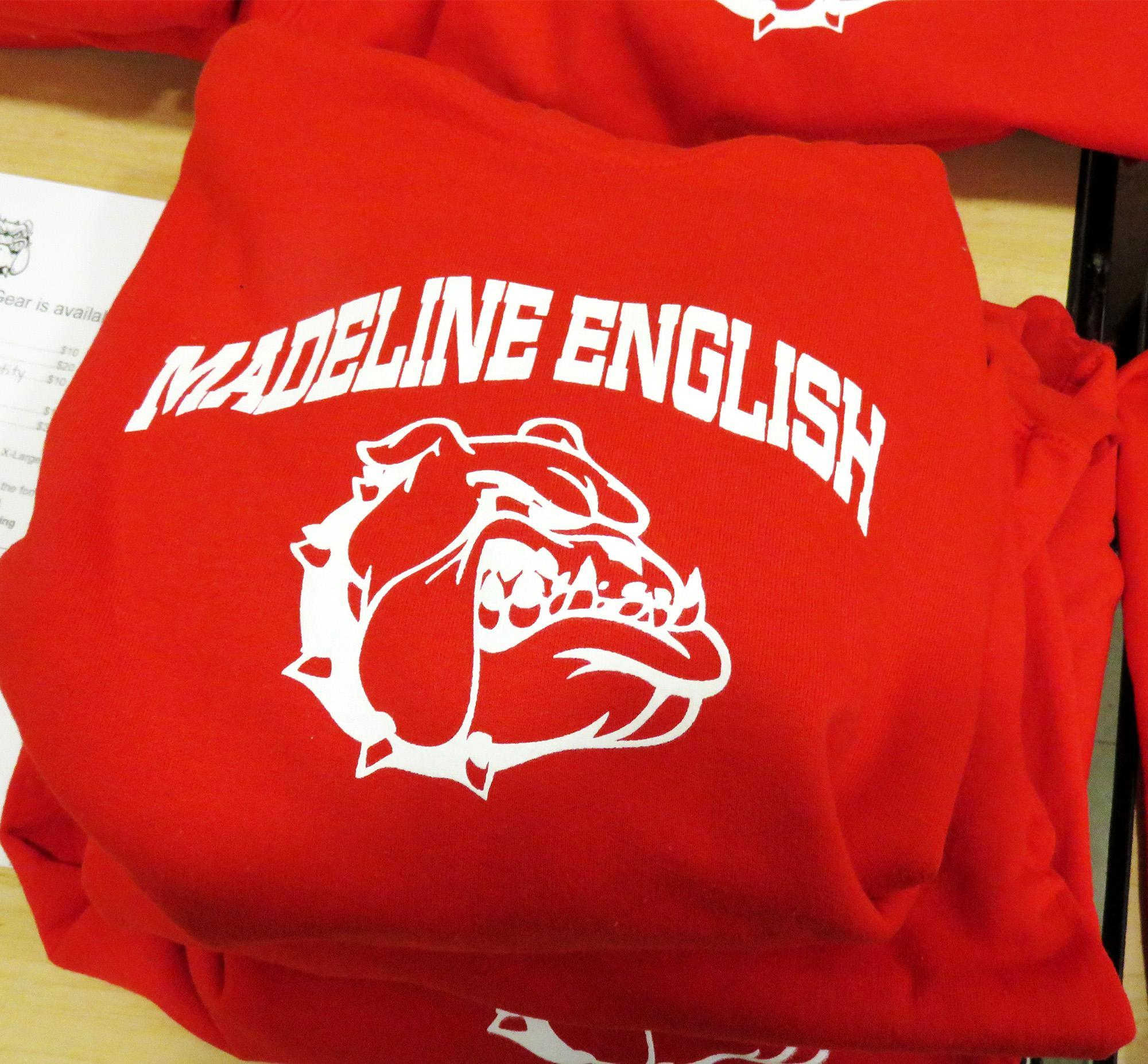 A red Madeline English sweatshirt with a cartoon face of a scowling bulldog