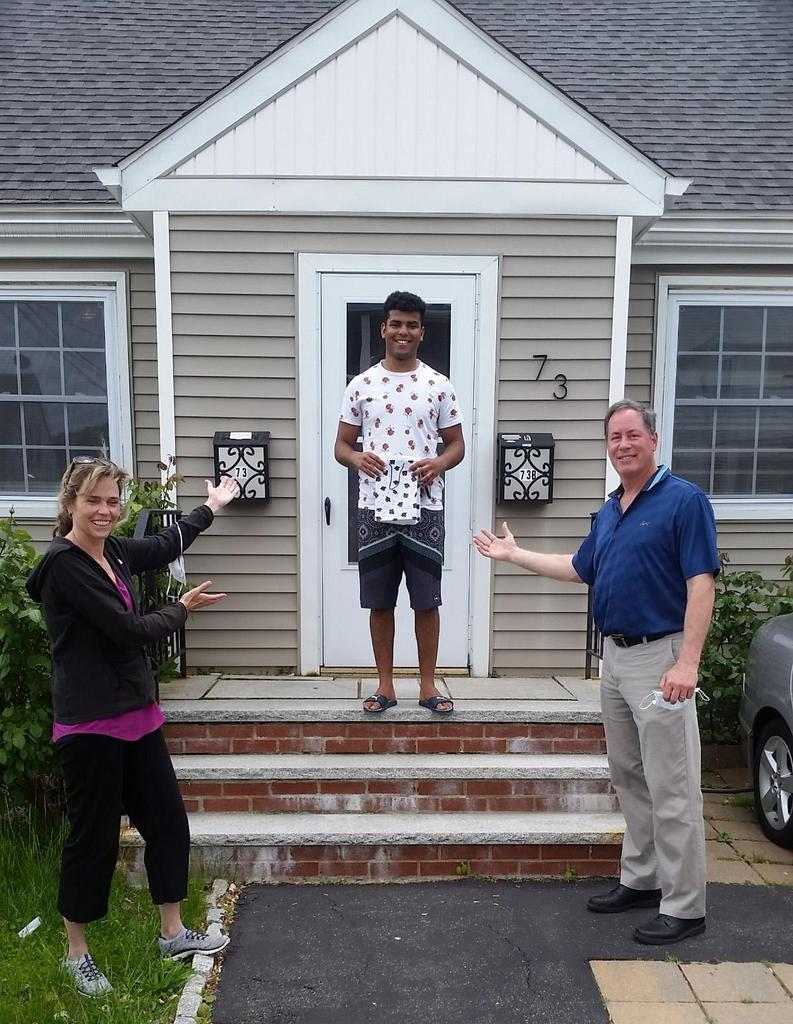 Mr. and Mrs. Steve Bond and a student on the front steps of his house