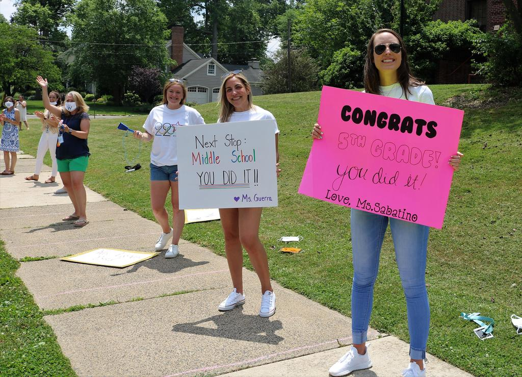Photo of teachers with signs, lined up for Wilson Grade 5 Clap Out Car Parade