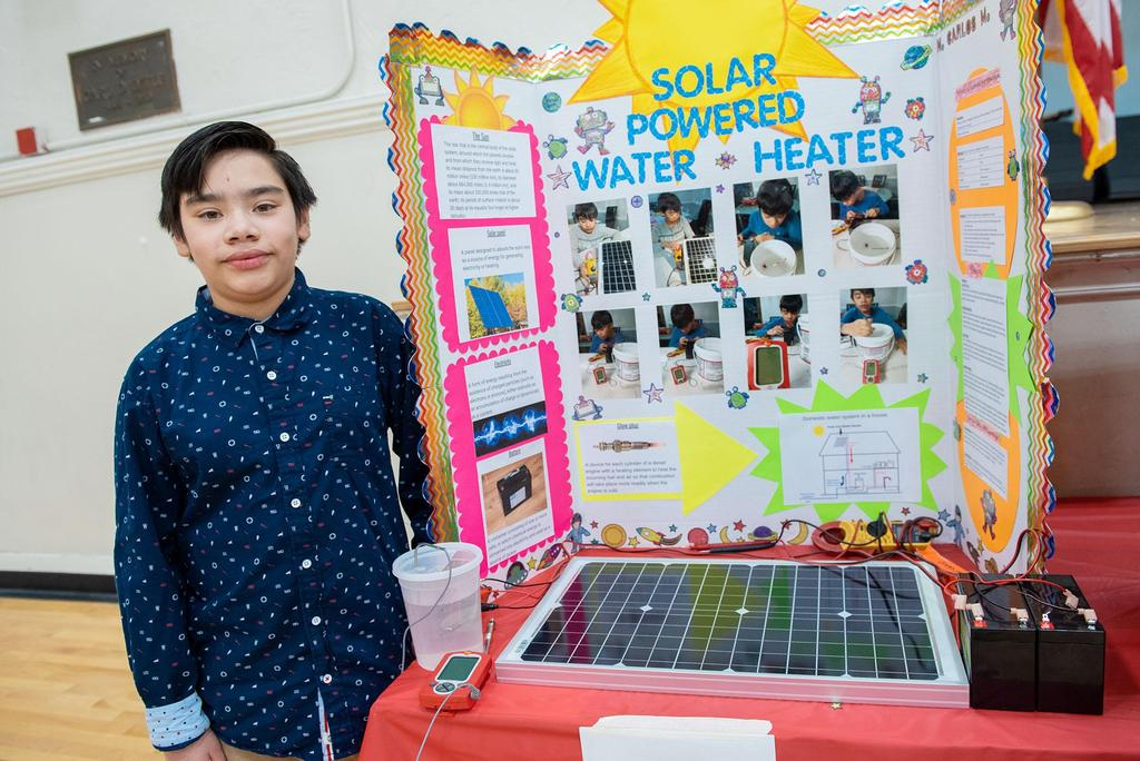 Posed photo of a student in front of his project on solar power