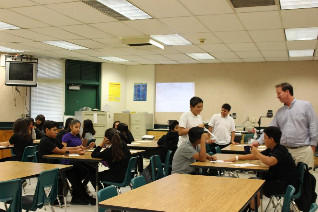 a teacher stands in class and converses with some students as students are seated at tables in a classroom