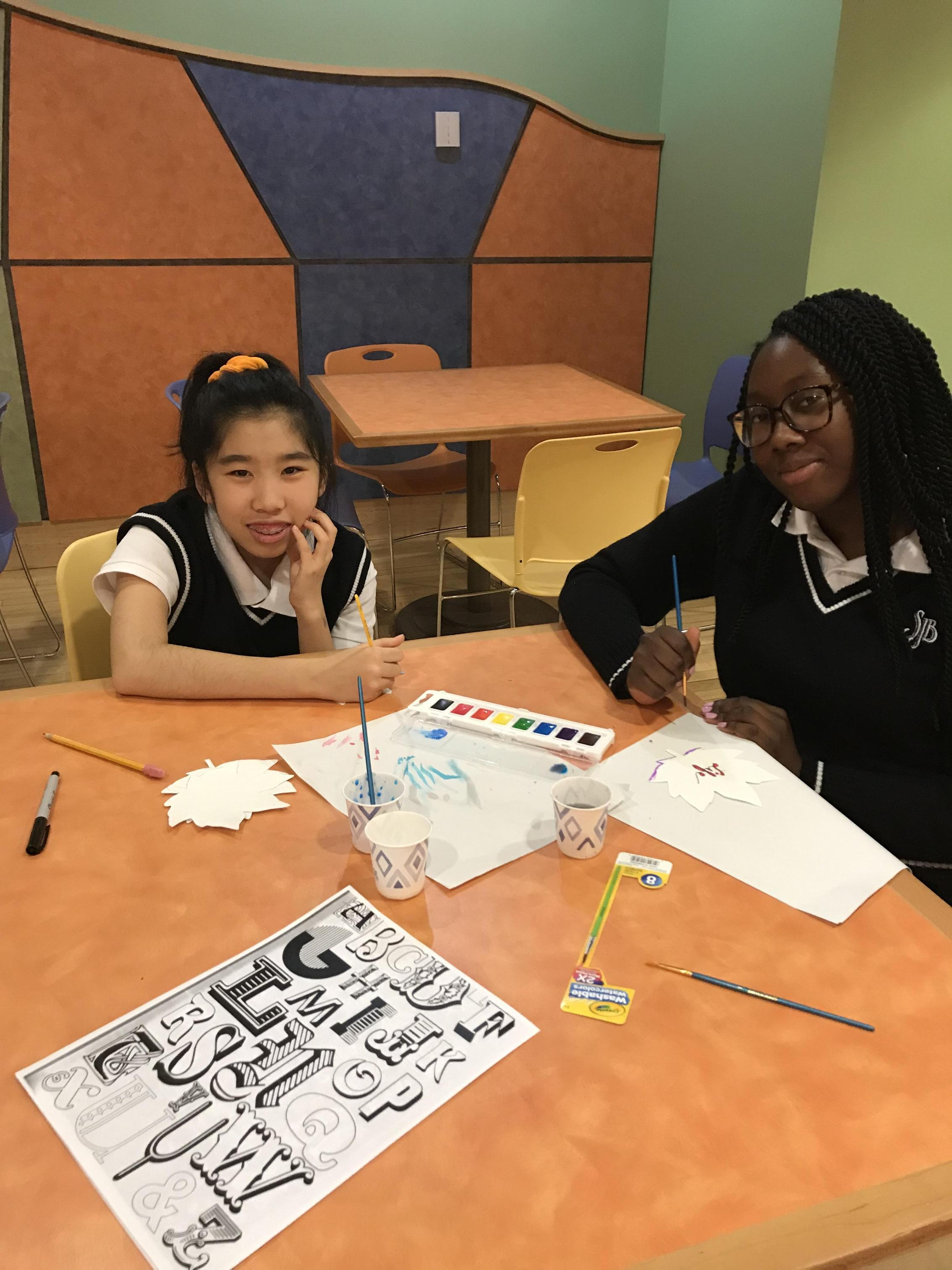 Two girls sit at table with art supplies