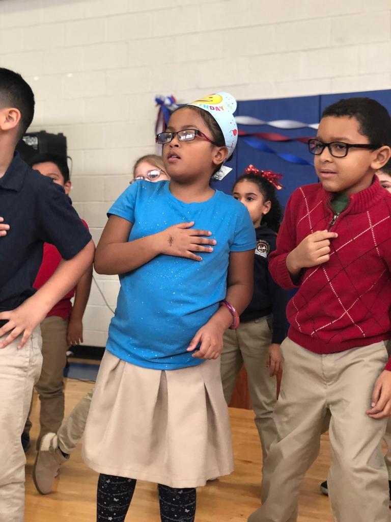 group of small children do the pledge of allegiance