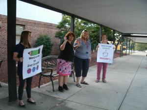 Teachers line the sidewalks and hold signs welcoming students back to school.