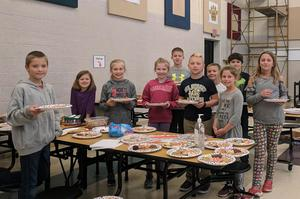 Student council members holding plates of cookies.