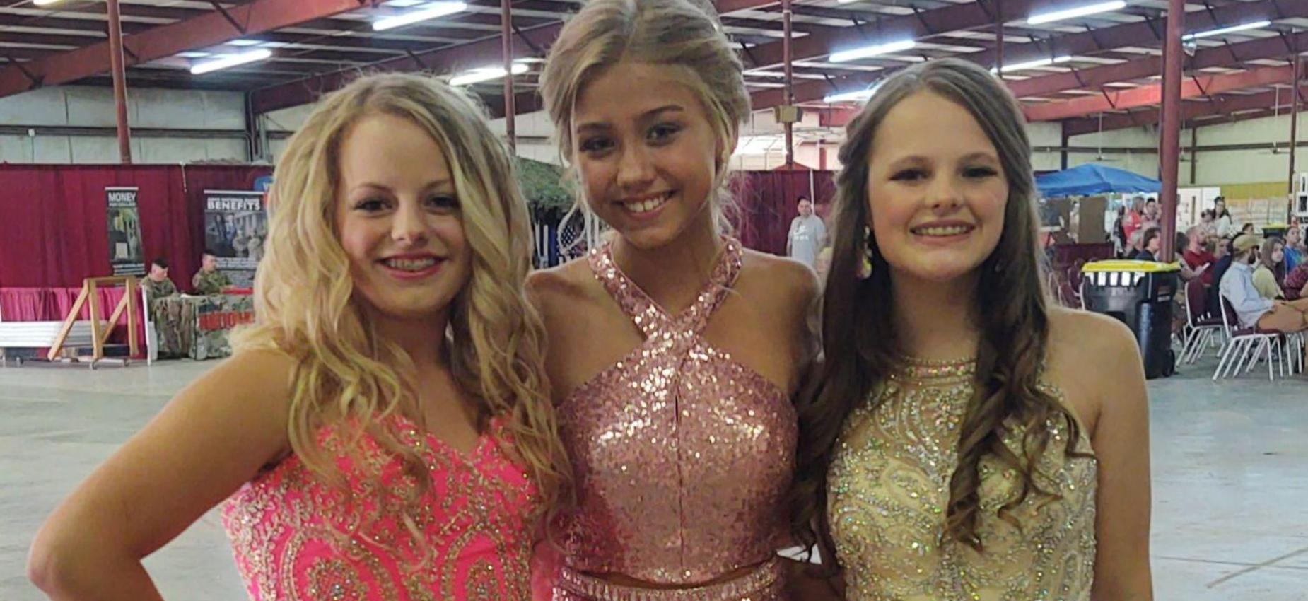 Three girls pose in pageant dresses.