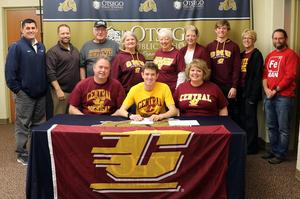 Picture of Zartman, family and coaches at his signing.