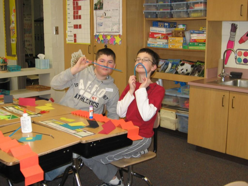 students create paper crafts at desks while posing with pipe cleaners on their faces