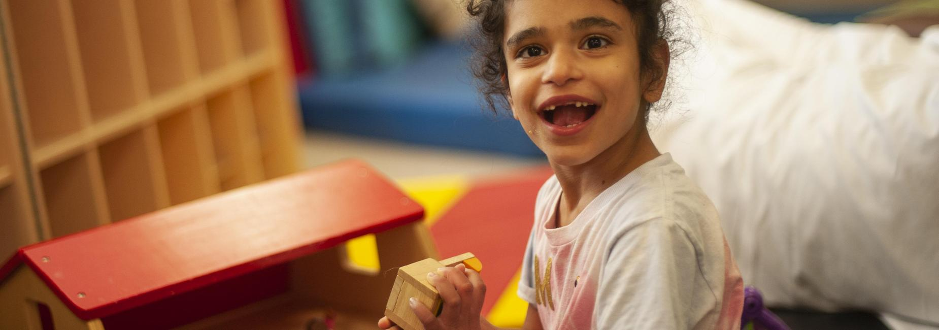 Student in middle program plays with wooden blocks.