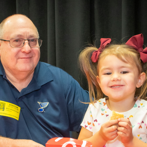 young girl having lunch at school with her grandfather