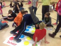 Group of male students playing the board game Twister.