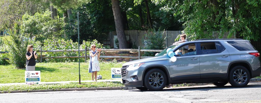 Photo of Franklin staff cheering on 5th graders as they pass by in Grade 5 Clap Out Car Parade