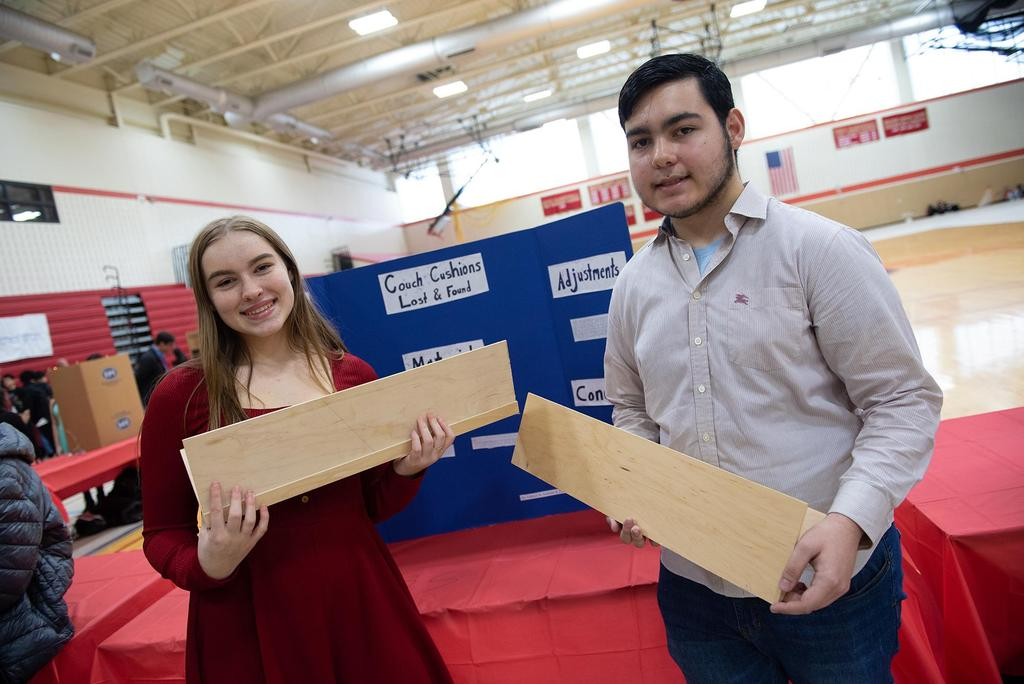 Two students hold pieces of wood