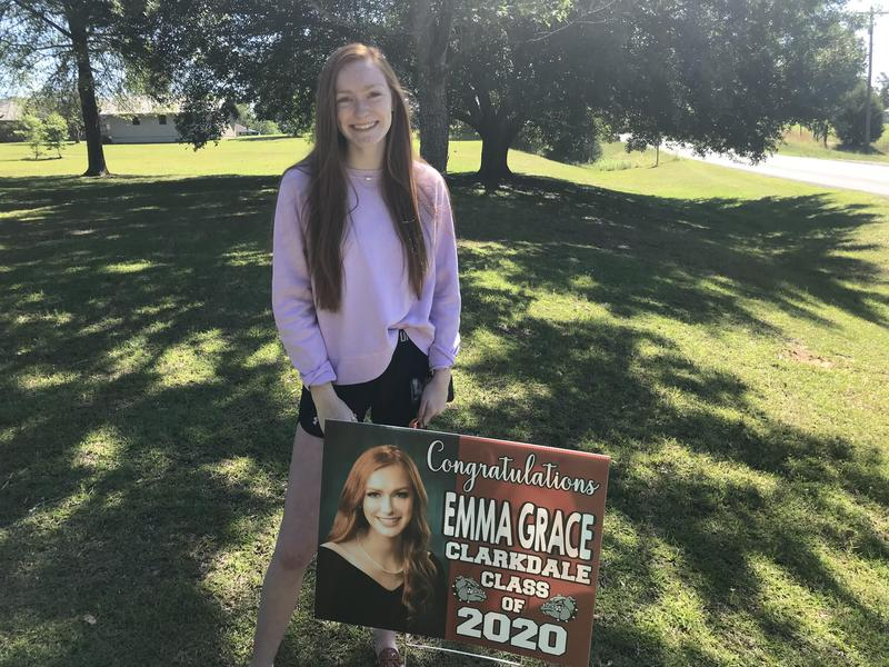 CHS Senior Emma Grace standing with her donated yard sign.