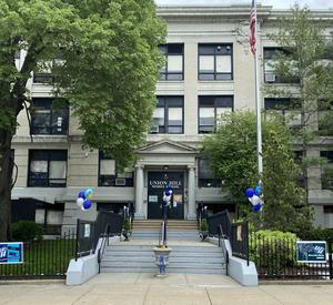 Front of school with blue and silver balloons