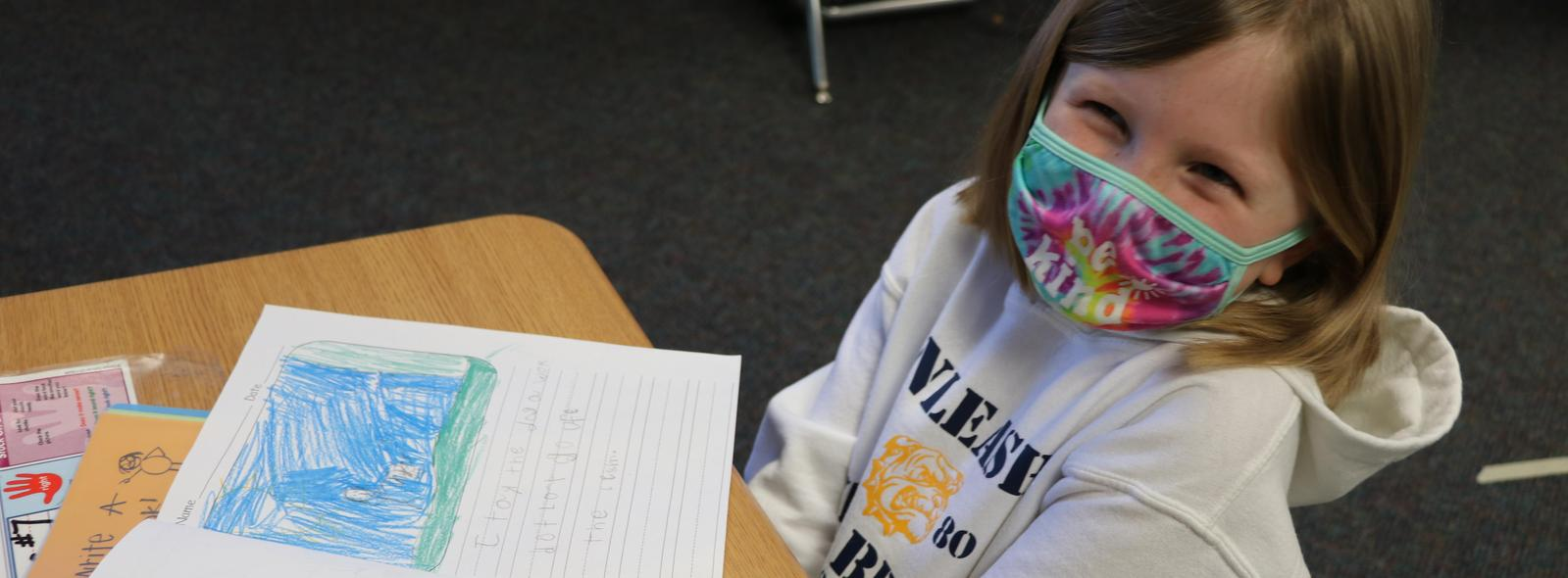 girl with tie dye mask on smiling at desk.