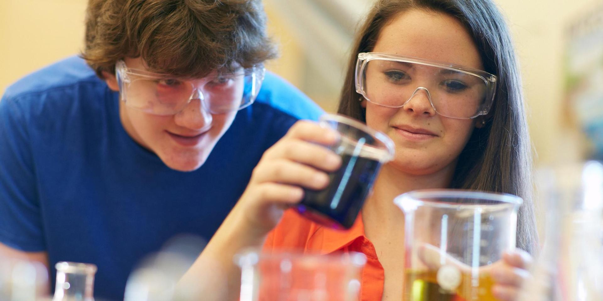 Two students conducting a chemistry experiment with fluids in beakers.